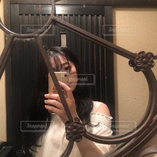 カメラにポーズ鏡の前に立っている女性の写真・画像素材[1451450]