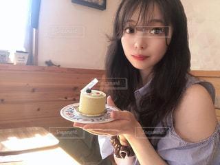 テーブルの上のコーヒー カップを保持している女性の写真・画像素材[1451493]