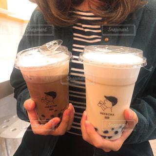コーヒー カップの横にあるオレンジ ジュースのガラスを飲む人の写真・画像素材[1561660]