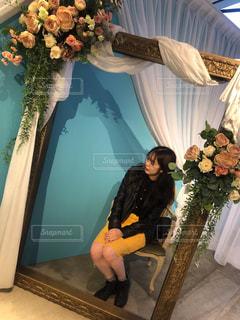 テーブルの上の花の花瓶の横に立っている人の写真・画像素材[1561803]