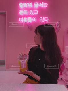 ピンクの画面の前に立っている女性の写真・画像素材[1561845]