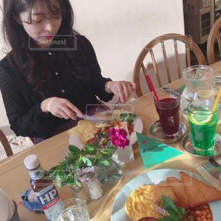食品のプレートをテーブルに座っている女性の写真・画像素材[1561892]