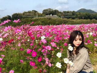 草にピンクの花の女性が立っています。の写真・画像素材[1605452]