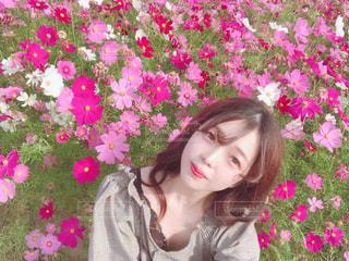 ピンクの花を身に着けている女性の写真・画像素材[1605455]