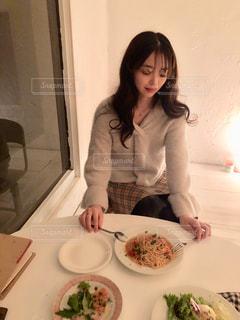 食品のプレートをテーブルに座っている女性の写真・画像素材[1643786]