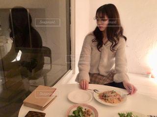 食品のプレートをテーブルに座っている女性の写真・画像素材[1643788]