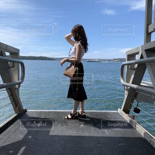 水の体の横にドックの上に立って人の写真・画像素材[1827642]