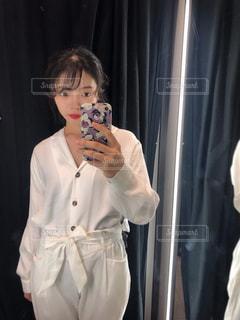 カメラにポーズ鏡の前に立っている人の写真・画像素材[1864771]