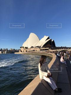 背景のシドニー ・ オペラ ・ ハウスの水の体の横に立っている人の写真・画像素材[1911394]