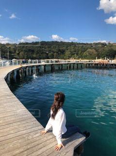 水域の隣のドックに座っている人の写真・画像素材[2138381]