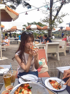 ピクニックテーブルの上に座ってピザを一切れ食べる女性の写真・画像素材[2138387]