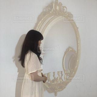 鏡の前に立つ人がカメラに向かってポーズをとるの写真・画像素材[2314714]