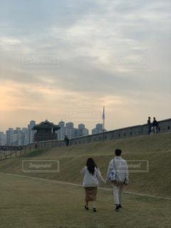 曇った空を歩く人々のグループの写真・画像素材[2822133]