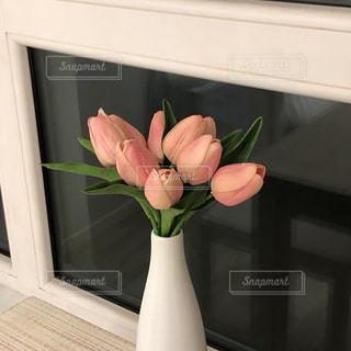 テーブルの上に座っている花で満たされた白い花瓶の写真・画像素材[2980729]
