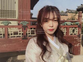 建物の前のベンチに座っている少女の写真・画像素材[2980827]