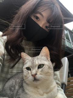猫の隣に座っている女性の写真・画像素材[3311909]