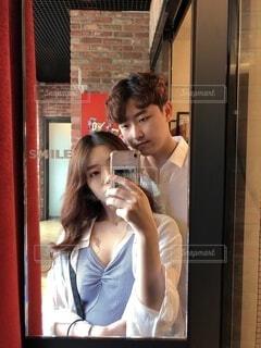 鏡の前に立ってカメラのポーズをとる男女の写真・画像素材[3645617]