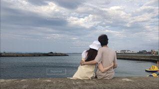 海辺で隣に座っている男女の写真・画像素材[3645621]
