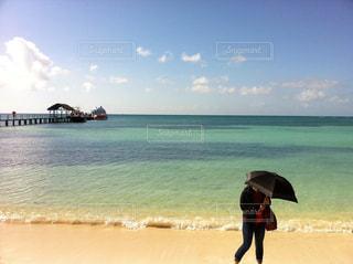 浜辺で、傘を持って歩いている女性の写真・画像素材[937479]