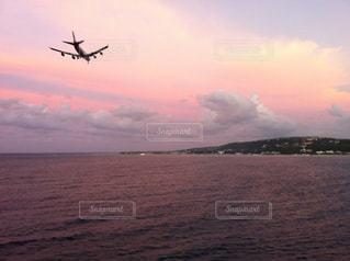 ジャマイカ モンテゴベイ 船から見た 夕焼けに着陸中の飛行機 。の写真・画像素材[938947]