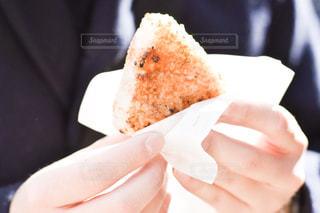 皿の上のケーキのスライスを持っている手の写真・画像素材[909266]