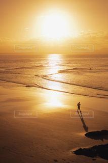 海の横にある砂浜のビーチに沈む夕日 - No.909872