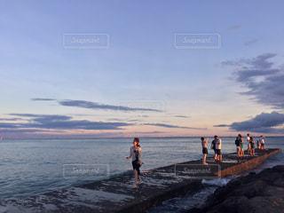 水の体の横に立っている人のグループの写真・画像素材[910481]