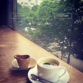 木製のテーブルの上に座ってコーヒー カップの写真・画像素材[911654]