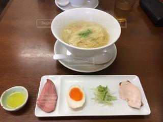 テーブルの上に食べ物のプレートの前にスープのボウルの写真・画像素材[915122]