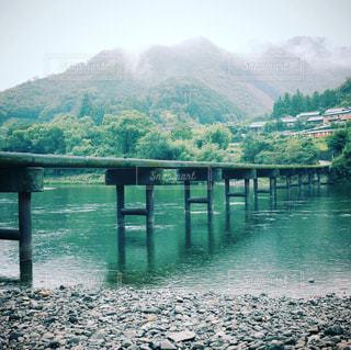 背景の山が付いている水の体の上の橋の写真・画像素材[914168]