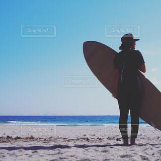 サーフボードを持ってビーチに立っている人の写真・画像素材[928095]