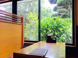 窓の横の木製のテーブルの上に座っているラップトップコンピュータの写真・画像素材[2199297]