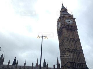 建物の側に時計と大きな背の高い塔の写真・画像素材[920979]