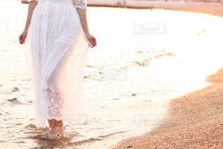 夕焼けの海辺を白ドレスで歩くの写真・画像素材[1990856]