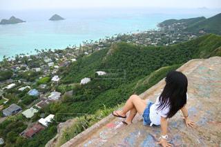 水を見下ろす岩の上に座っている人の写真・画像素材[1231175]