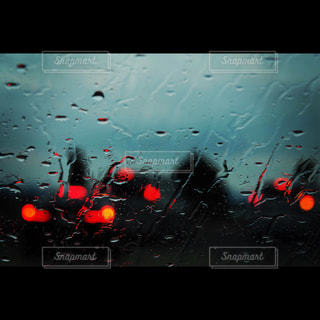 近くに雨の中の赤い光のアップの写真・画像素材[926975]