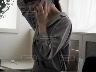 頭をかきながらスマホで電話してる女性の写真・画像素材[1170729]