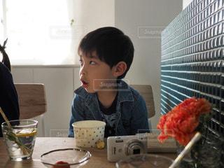 窓の前のテーブルに座っている男の子 - No.1171832