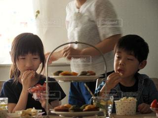 おやつ中の子どもと準備する親の写真・画像素材[1171833]