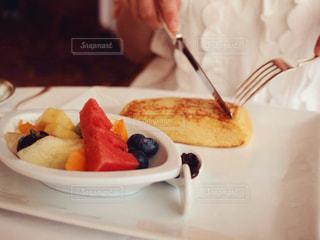 フォークで食べ物のプレートを持っている人の写真・画像素材[1210380]