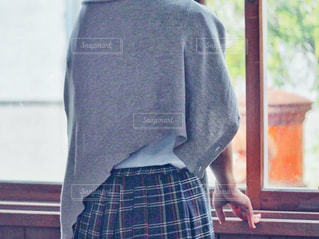 窓の前に立っている女子高生の写真・画像素材[2116604]
