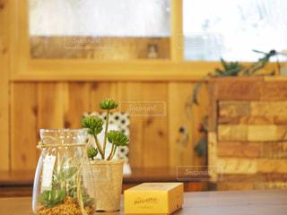 カウンターに座っている花でいっぱいの花瓶の写真・画像素材[2439463]