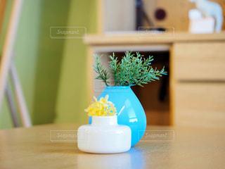 木製のテーブルの上に座っている花瓶の写真・画像素材[2439480]