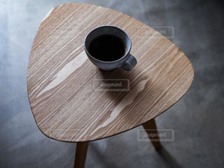 木製のテーブルの上に座っているコーヒーを一杯の写真・画像素材[3431897]
