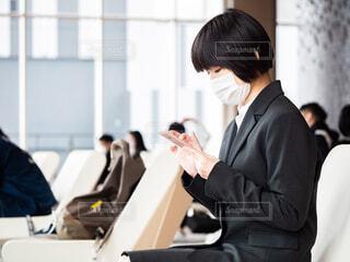 ロビーでスマートフォンを触りながら待ち合わせをしているマスクをつけた女性の写真・画像素材[4286401]