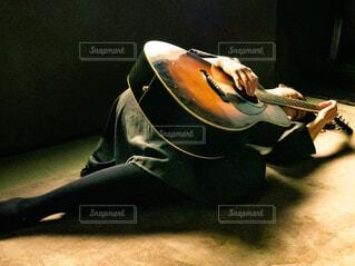 ギターを抱えて寝込んでいる女性の写真・画像素材[4358102]