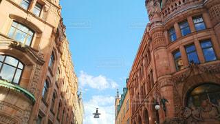 大きなレンガの通りの側に時計と建物 - No.928658