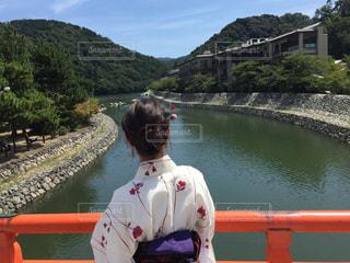 京都の橋の上から川を眺める女性の写真・画像素材[928875]
