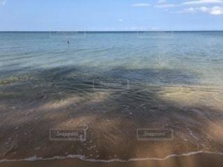 水の体の横にある砂浜のビーチの写真・画像素材[1015650]
