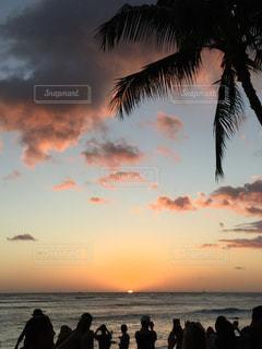 ビーチでの背景の夕日に人々 のグループの写真・画像素材[928959]